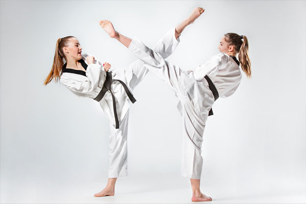Two people doing side kicks in ATA martial arts uniforms